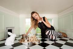 Young woman playing chess with rabbit - stock photo