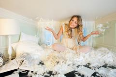 Young woman in small room, throwing pillow feathers - stock photo