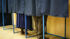 Unrecognizable people voting inside booths Stock Footage