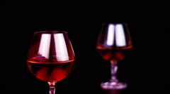 Man's drinking cognac on black background - stock footage