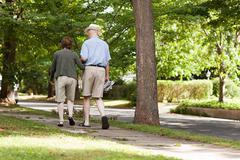 Senior couple walking in neighborhood - stock photo