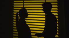 Man makes a gift to a woman and gets a kiss. Silhouette. Slow motion. Close up - stock footage
