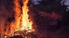 Slow motion shot of elder woman burning dry branches on the bonfire - stock footage