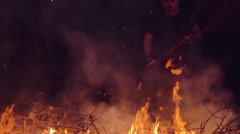 Slow motion shot of man burning dry branches on the bonfire Stock Footage