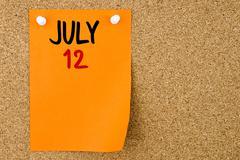 12 JULY written on orange paper note - stock photo
