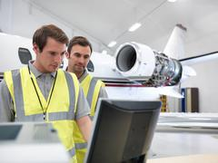 Engineers in aircraft hangar with jet - stock photo