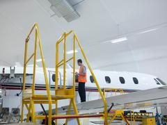 Engineer inspects jet aircraft - stock photo
