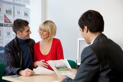 Couple visiting estate agents office - stock photo