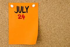 24 JULY written on orange paper note - stock photo