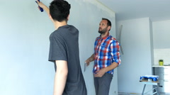 Father reprimanding his son while painting wall at their new home Stock Footage