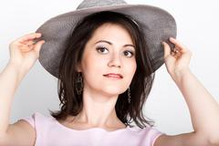 Beautiful young brunette woman holding a broad-brimmed hat, she hides her face Stock Photos