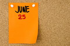 25 JUNE written on orange paper note - stock photo