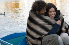 Man and woman snuggling under blanket Stock Photos