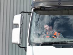 Driver looking in truck mirror Stock Photos
