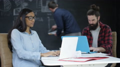 4K Young team in startup company working together & discussing business plan - stock footage