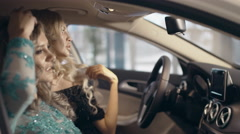 Two gorgeous models in long evening dresses sitting in the car and posing for Stock Footage