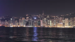 Time-lapse camera pan of skyline of office blocks on Hong Kong Island at night Stock Footage