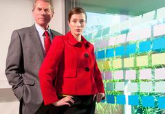 Two business people with wall of sticker - stock photo