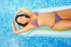 Woman relaxing on lilo in swimming pool - stock photo
