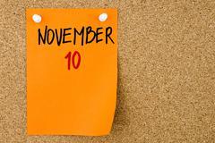 10 NOVEMBER written on orange paper note - stock photo