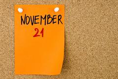 21 NOVEMBER written on orange paper note - stock photo