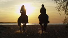 Silhouette of Two Young Women Riding Horses on Beach - stock footage