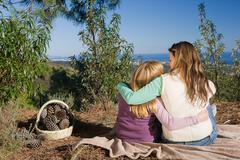 Mother and daughter hugging rural scene - stock photo