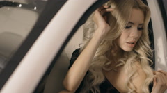 Photosession of the beautiful blonde in evening dress posing near the car Stock Footage