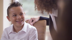 4K Young brother & sister at breakfast table, their mother gives them a kiss Stock Footage