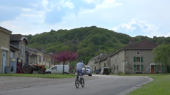 Typical french small village with kid biking, sunny summer day Stock Footage