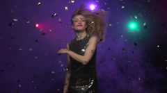 Girl in brilliant dress dancing under glitter confetti. Slow motion - stock footage