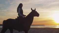 Silhouette of Young Rider on Horse at Beach in Sunset Light. Stock Footage