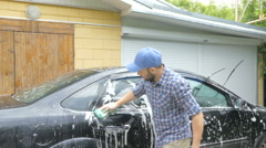 Man washing his black car near the house. Stock Footage