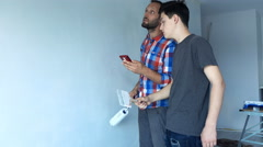 Father and son talking and using smartphone while painting wall at their new hom Stock Footage