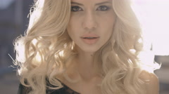 Gorgeous blonde with long curly hair posing for camera flashes Stock Footage