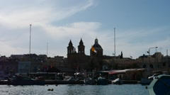 Marsaxlock against sun - hyperlapse with clouds, boats and people motion Stock Footage