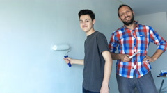 Portrait of happy father and his son painting wall at their new home Stock Footage