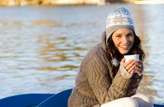 Woman holding mug in row boat Stock Photos