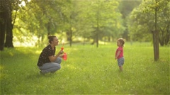 Mother and girl blowing soap bubbles outdoor. Parent and kid having fun in park. - stock footage