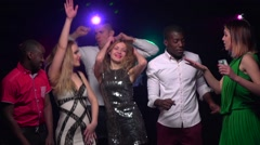 Friends of different nationalities dancing at party. Close-up. Slow motion Stock Footage