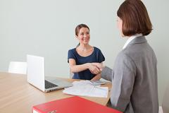 Young woman shaking hands with financial adviser - stock photo