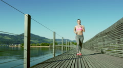 Young woman runs on a bridge Stock Footage
