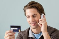 Young man on the phone with credit card Stock Photos