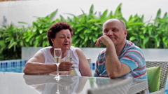 Happy smiling elderly couple drinking champagne in a tropical villa - stock footage