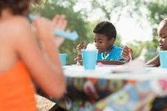 Children sitting at picnic table at birthday party - stock photo
