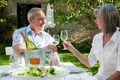 Mature couple having lunch outdoors - stock photo