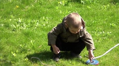 Young boy playing with measuring tape in the backyard  Stock Footage