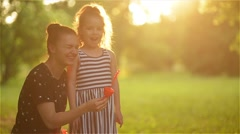 Beautiful mother with her daughter in nature making soap bubbles and laughing - stock footage