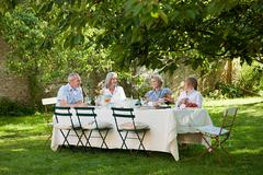Family having lunch outdoors - stock photo