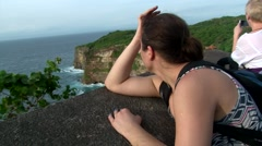 BALI. INDONESIA: girl on the cliff and looking at the ocean in Uluwatu Temple Stock Footage